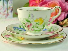 Royal Stafford Sweet Pea pattern vintage English bone china teacup, saucer and tea plate trio. c.1950s Beautiful hand painted sweet pea flowers in pink, blue and yellow with green foliage and gold gilded rims. Teacup 8.5cm wide at the rim x 7cm tall approx. with a little sweet pea flower inside the rim. 14cm wide saucer and 16.5cm wide side or tea plate. Made by Thomas Poole and Gladstone China, Longton, Staffordshire, England. c.1950s In excellent condition.