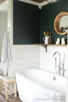 Half shiplap walls with deep green on top - love this oversized soaker tub and the wood shelf over the bathtub