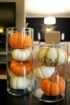 Tiny pumpkins/gourds in hurricane glass or tall vase.