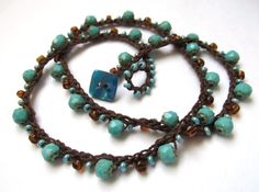 beautiful, one of a kind beaded crochet necklace made of Czech faceted glass beads in a beautiful dark, turquoise and fire polished Czech glass seed beads in pale aqua and clear chocolate brown crocheted onto soft, fluid cotton crochet thread in dark brown. This is a great, way to add a little luxurious touch of rich color to your everyday wardrobe and also makes a wonderful 3x wrap bracelet for a 6 - 7 wrist. This piece measures about 20 and fastens with a lovely teal colored plastic…