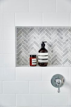 White subway tiles frame a gray marble herringbone tiled shower niche.