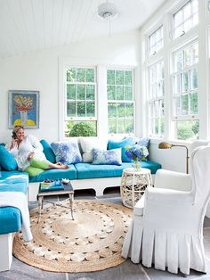 Despite its small size, this sunroom feels much larger because of its bright white walls and abundance of windows. A radiant heat system is installed under the bluestone pavers to keep this room cozy even during the winter months. The sectional sofa is a custom, built-in look, maximizing the seating space in this small room. (Photo: Peter Murdock) Love that rug!