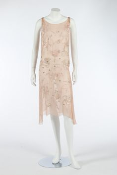 A floss silk embroidered pale pink chiffon cocktail gown, circa 1927. embroidered in pastel to ivory silks with stylised blossom and palmettes,with pearlised bugle beads and scattered with rhinestones, bust 81-86cm, 32-34in.