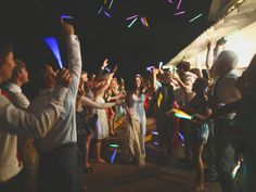 Guests tossed their glowsticks into the air as Kevyn + Andrew exited their reception through a tunnel of color. | The Sonnet House | Photo by J. Woodbery Photography