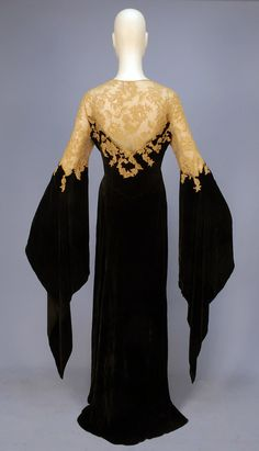 LOT 853 - VELVET & LACE DESHABILLE, with WIZARD SLEEVES, 1930's. -  Black bias cut silk panne velvet wrap with off center self button & loop closure, having sheer ecru Alencon lace bodice top & applique to velvet, curved skirt gores, lace topped long, pointed sleeve open from above the elbow, inside tie at waist - Whitaker Auctions Photos