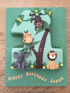 Jungle themed first birthday cake. With elephant, lion, monkey and giraffe.