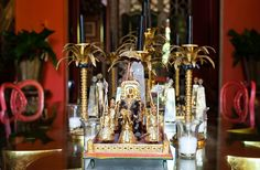 Displayed on the dining table are gilded Indian figures of maharajas riding elephants and golden bronze palm candlesticks by Codognato, the famed Venetian jeweler.