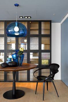 A Fascinating Round Wooden Table With Modern Black Chair And Charming Blue Glass Table Decors And Cool Chandelier With Built In Black Cabinet Dark Interior Color Schemes with Spacious Living Area Wooden Floor living room, Interior design