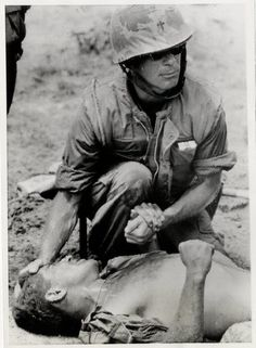 A U.S. Navy chaplain gives comfort to a wounded member of the U.S. 1st Marine Regiment at the site of the mining of a convoy truck on Highway One, outside Quang Tri City Oct. 11. Three marines were...