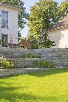 Inspiration für Ihre Außenanlage mit Höhenunterschieden. Die terrassierte Positionierung der Romano Mauer bietet Ihnen im Garten tolle Gestaltungsmöglichkeiten mit angelegten Beeten. #rinnbeton #design #gartengestaltung