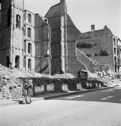 Girls walking arm in arm along a row of ruined buildings in a residential area, Berlin, 1947