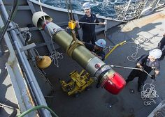 Sailors assigned to the guided-missile destroyer USS Stout (DDG 55) transport an M-46 Torpedo.