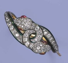Victorian enameled and diamond bangle. Designed as two interlocking snakes with old-cut diamond head and body to the slightly articulated ruby eyes and green enamel tails, mounted in silver and gold, ca. 1850.