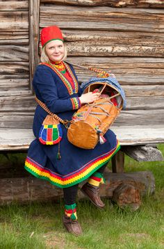 """From the north of Sweden, a Sami folk costume. The young mother is wearing a kirtle from Arjeplog made of elk chamois leather. The kirtle is a modern version with a zig zag design round the neckline and the wrists. She is also wearing the traditional cap and a woven belt, and carrying a leather cradle, a """"gietgam"""" (in South Lule Sami language)."""