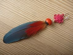 Buddhist Node Earring: Guairuro seed, parrot feathers.