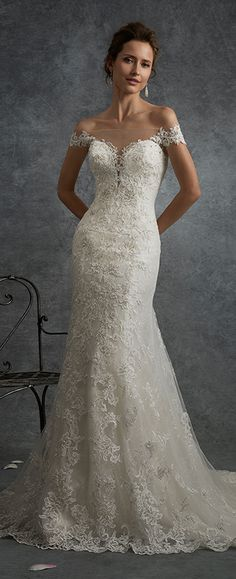 Off-the-shoulder lace fit and flare wedding dress with hand-beaded appliqués, plunging sweetheart bodice, low illusion back adorned with lace.