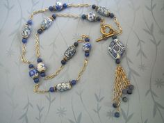 Blue and white necklace with gold tone chain and porcelain beads necklace.Small round sodalite accent beads and front clasp.