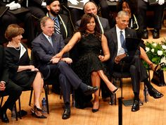 First lady Michelle Obama and President George W. Bush, flanked by President Barack Obama and former first lady Laura Bush, share a moment during a memorial service for five police officers were killed and several injured during a shooting in downtown Dallas last Thursday night, Tuesday, July 12, 2016, at the Morton H. Meyerson Symphony Center in Dallas.