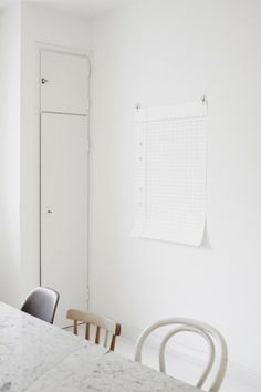 interior detail—a spare white-on-white space with handsome details and a harmonious trio of mismatched chairs