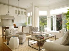 Family room right of kitchen is filled with a light gray roll-arm sofa facing two heather gray tufted chairs across from a brickmaker's coffee table placed atop a natural woven rug.