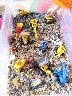 Rocks in a bin as an alternative to sand. Trouble with play sand every time we use it as it gets all over the grass and kills it. Rocks or even beans in my son's water table would work better. I like this idea from Pink and Green Mama.