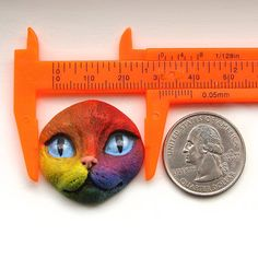 Rainbow Cat Face Cab - item #3358 Meow! My colorful cat face with big blue eyes is purrrfect for your feline creations. This hand painted polymer clay face is ideal for creating art jewelry, brooches, lapel pins, magnets, beaded art dolls, mixed media artworks, amulet bags or purses, fetish dolls, assemblages, collages, ornaments, whatever you can imagine.  Face measures: 1 1/8 inches tall x 1 3/16 inches wide x 1/2 inch thick 2.9 cm tall x 3.0 cm wide x 1.3 cm thick 29 mm tall...