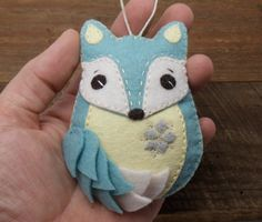 **NO LONGER ACCEPTING CUSTOM ORDERS OR ORDERS FOR PERSONALIZATION** This little fox was all hand stitched, embroidered, and appliqued, featuring a poofy tail created with individually hand cut pieces of felt and a glass bead embellished snowflake on his tummy.  A tiny heart and the year 2016 are hand stamped on an aluminum tag that adorns the back of the ornament.  Lightly stuffed with poly-fill and finished with a loop of cotton cord for hanging.  Measures approximately 3 3/4 long by 2 1/2…