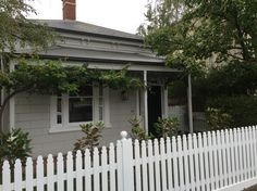 Dulux: house - Vanilla Quake. Trim and door - Monument. Fence and wood frames - Leixcon Quarter.