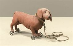 A BROWN-FELT STEIFF DACHSHUND ON WHEELS