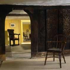 Detail of the original plank and muntin screen decorated with paintings from C15th in the Parlour, looking through to the Hall at Marker's C...