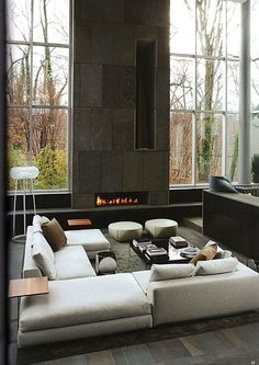 Modern,+minimalist+design+in+this+tall+space+featuring+stone+fireplace+surround,+floor+to+ceiling+windows,+and+white,+U-shaped+modern+sectional+sofa+with+twin+round+ottomans+and+black+glass+coffee+table.+