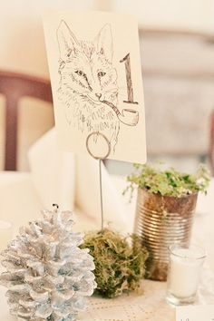 Woodland creatures double as adorable sketches for table numbers. A glittery pinecone brings a bit of chic to the rural outdoor elements.
