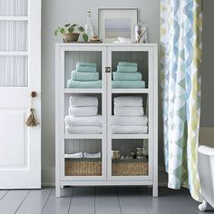 Clean-lined classic cabinet frames books, linens, cookware and collectibles in white, with dove grey shiplap backing and shelves for pleasing contrast. Designer Mark Daniel based this version on an antique cabinet seen in Mahatma Ghandi's South African home, updating its traditional look with a pared-down silhouette, fresh color and a single brushed nickel knob latch as a glistening accent.