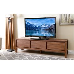 The Avion 70-inch Walnut Wood Entertainment Center will add a stylish and modern touch to your living room or den. It features a simple design with three drawers for storage and a rich walnut finish.