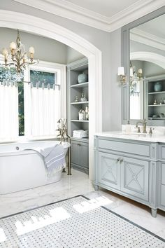 """""""The master bath is a traditional design with transitional details,"""" says Hepfer. """"It's neutral enough to feel and look timeless."""" The walls and cabinetry are painted Benjamin Moore's Stonington Gray and Coventry Gray, respectively. The sink and BainUltra tub feature Perrin & Rowe fittings, the sconces are by Hudson Valley Lighting, and the chandelier is by Fine Art Lamps."""