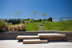 Stepping stones and wooden stairs connect the garden to the pool deck.