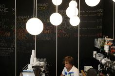 relaks cafe and bike repair shop by super super + moko architects Coffee Shop Menu, White Cafe, Bike Store, Repair Shop, Light Bulb, Chandelier, Ceiling Lights, Architects, Shopping