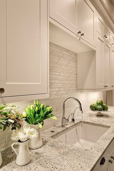 Lovely creamy white kitchen design with shaker kitchen cabinets painted Benjamin Moore White Dove, Kashmir White Granite counter tops, polished nickel modern faucet and Vetro Neutra Listello Sfalsato Glass Mosaic- Bianco tiles backsplash.  Benjamin Moore White Dove.