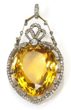 An antique citrine and diamond pendant-brooch, circa 1895. Centring a heart-shaped citrine weighing approximately: 36.00 carats; mounted in silver-topped fourteen karat gold.