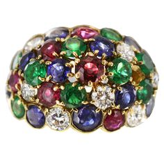 Van Cleef & Arpels expressed glamorous 60's style in this domed ring. Rows of alternating gems exemplify the true meaning of jewel tones. Round-cut wine-red rubies, rich emeralds, multi-hued sapphires and glittering diamonds curve gently to fit the simple yet elegant 18K gold setting.