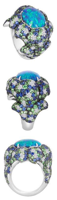 Australian Black Opal Ring, This one-of-a-kind design features an Australian black opal that presents us with deep colors of blue and green. The center stone is prong-set in an 18k white gold setting that is studded with a variety of precious gemstones that include diamonds, blue sapphire, and tsavorite. These stones were specifically chosen to compliment the hues exhibited in the opal itself. Opal Weight: 7.75 cts