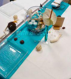 Pour une décoration épurée mais chic, Pink Event vous propose cette table marine. Pour cette table il vous faudra : un chemin de table turquoise, un ruban filet, un vase aquarium pour un centre de table original avec à l'intérieur des coquillages, un photophore (+ bougie), des branches tortueuses ivoires, et pour embellir votre table on vous propose d'y ajouter des étoiles de mer, du Bois flotté, des galets, des boules en rotins et même une ardoise.