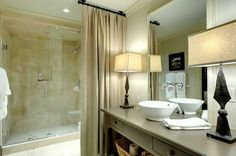 Curtain concealing toilet. Lamps on the counter instead of sconces. Design by Betty Burgess.