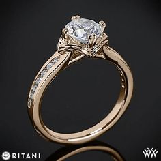 This Diamond Engagement Ring is from the Ritani Modern Collection. The graceful 4 prong head will perfectly house the round diamond center of your choice. The shank holds gorgeous channel-set Round Brilliant Diamond Melee (0.17ctw