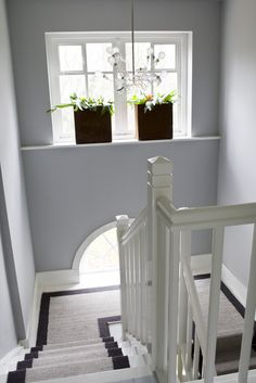 Witte houten trap met dubbel bordes, bekleed met wollen loper in twee kleuren.