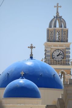 Picture of the Blue Church Domes And Clock Tower Side Aligned Against Blue Sky - Fira, Santorini, Greece