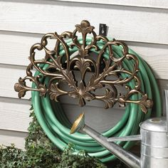 Avoid frustrating knots in your garden hose with the Filigree Decorative Hose Holder. This American-made garden hose holder measures long by high and holds up to 50 feet of hose in a neat coil. Manufactured from powder-coated cast aluminum, i Garden Hose Storage, Garden Hose Holder, Cool Diy, Hose Hanger, Yard Ornaments, Whitehall Products, Grades, Filigree Design, Patio