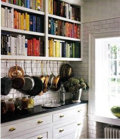 Cookbook shelves. Cookbooks by color. Pot rack. Subway tile. I don't like the gold-colored pulls, but that's minor...