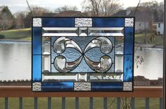 This stained glass window panel has a Victorian bevel cluster in the center and is surrounded by a pale blue glass. There is a 10 piece beveled border around the pale blue background and then then the panel is finished off with a medium blue and clear granite border. The overall size of the panel is approximately 16 3/4 by 12 1/4 and there are rings in the corners so the panel can be hung in either direction.   The patina on the solder is black and the frame is left in silver tone zinc.