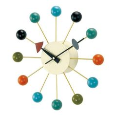 The classic design of the George Nelson Ball 13 in. Wall Clock - Walnut features iconic style and sleek contrast. The cool metal spindles feature warm,.